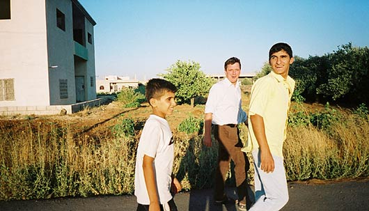 Mohammed, John and Yusuf stride in evening sunlight in the village